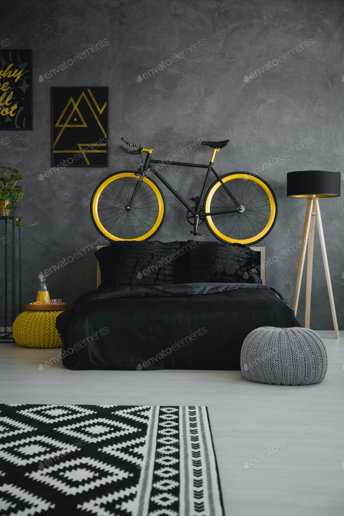 Bike above black bed in modern grey bedroom interior with patter