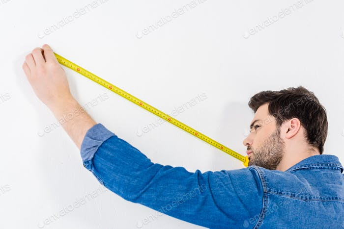 man measuring wall with tape measure on white