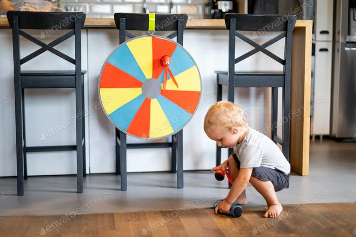 Smiling little child boy playing toy dart at home