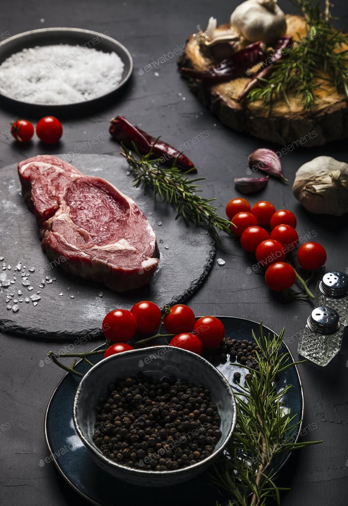 Raw beef entrecote with rosemary, salt and pepper on a round slate.