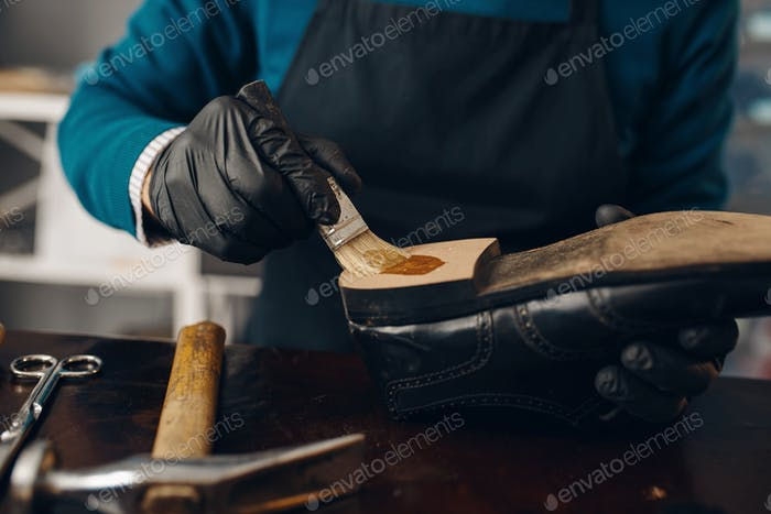 Shoemaker smears glue to the shoe, footwear repair
