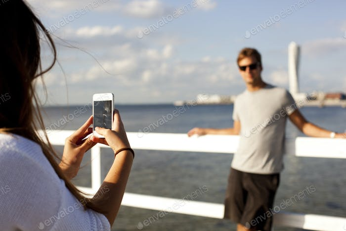 Young woman photographing boyfriend by pier over sea