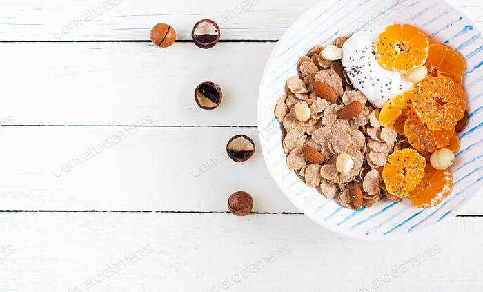 Bowl of flakes with yogurt and tangerine on white wooden table.