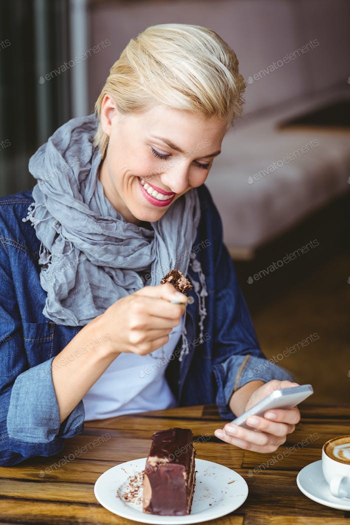 Smiling blonde enjoying a piece of chocolate cake at the cafe