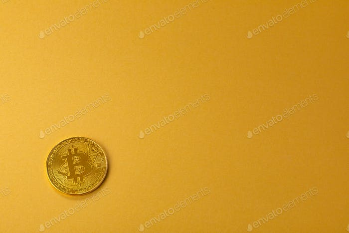 Gold bitcoin cryptocurrency coin on gold yellow backgound