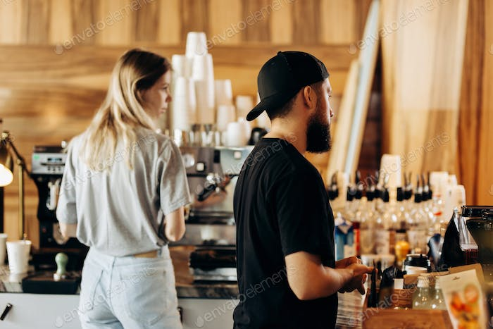 Two young stylish people,a thin blonde girl and a man with beard,wearing casual clotes,cook coffee