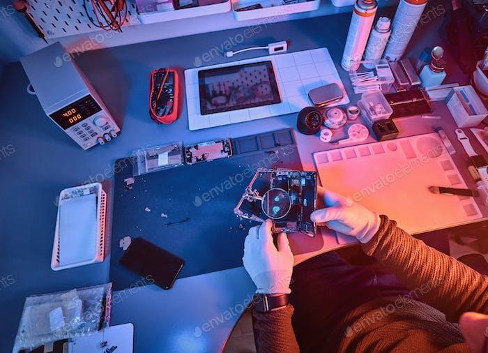 Elektronisch iker hält ein modernes Smartphone mit einem gebrochenen Körper