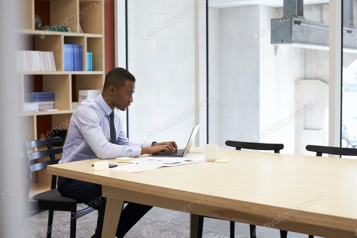 Young black businessman working alone in an office