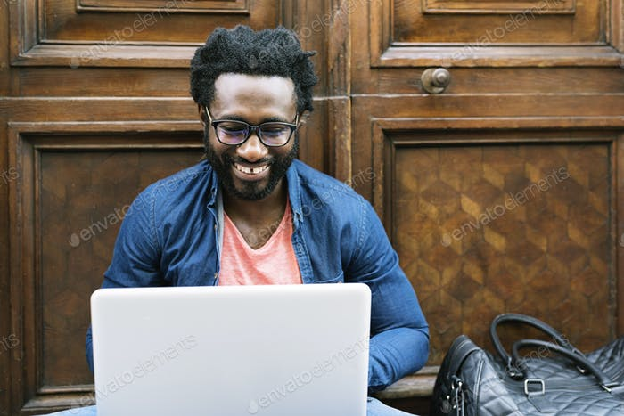 Portrait of african man sitting outside with laptop.