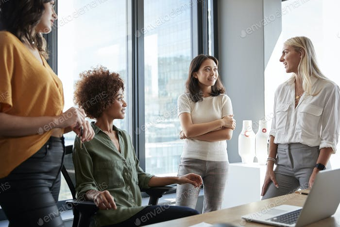 Four female colleagues in discussion at a desk in a creative office, three quarter length, close up