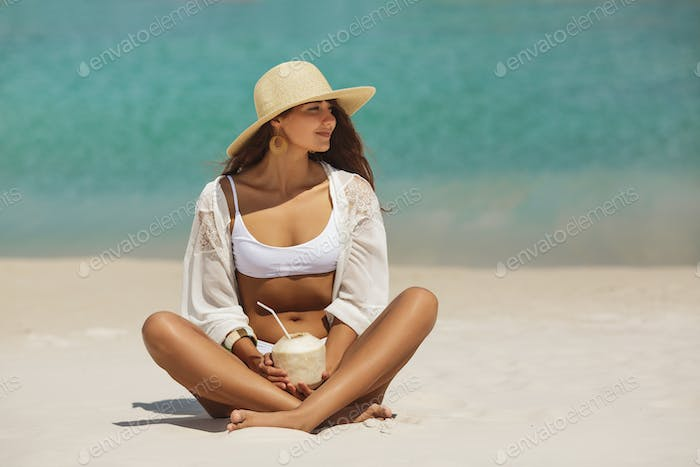 Tanned Woman in Bikini with Coconut on the Beach