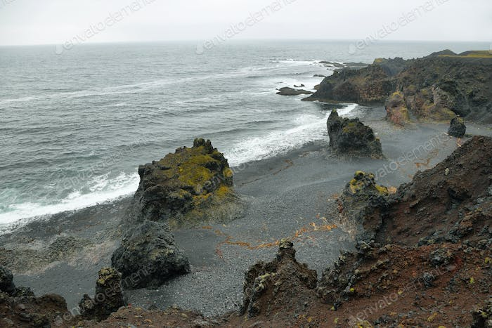 Rock formations in black sand beach of Djupalonssandur