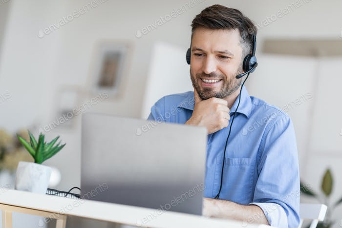 Hotline Support Service. Male call center operator in headset working with laptop