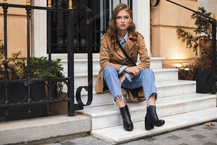 Young attractive woman in trench coat and jeans dreamily looking