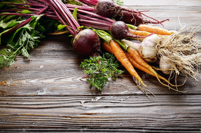 Fresh organic beetroots green garlic and carrots on kitchen wood