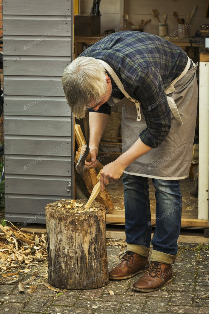 Craftsman woodcarver bending down and holding a hand axe, cutting a small piece of wood on a