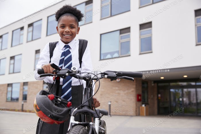 Portrait Of Female High School Student Wearing Uniform With Bicycle Outside School Buildings