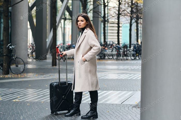 Thumbnail for Beautiful stylish girl standing on city street with little suitcase