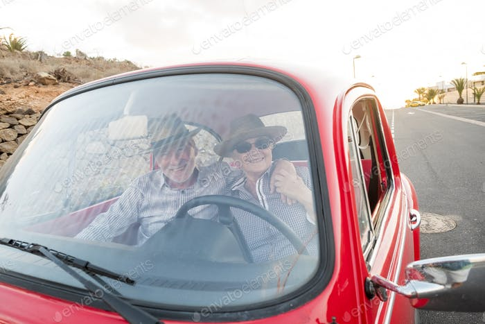nice adult couple hug and love inside a red old vintage car