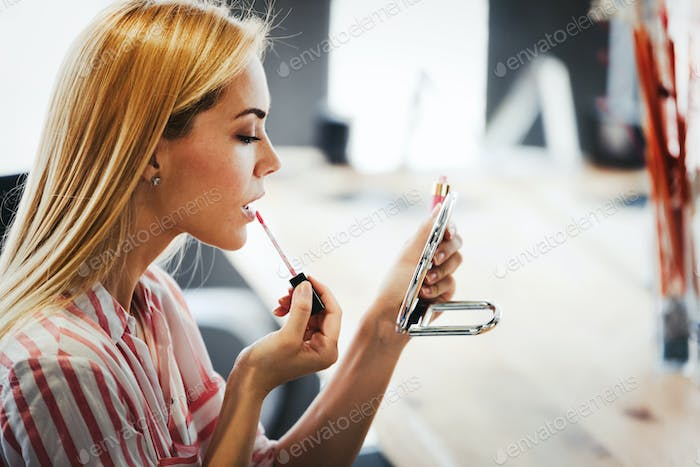 Young woman making make-up near mirror