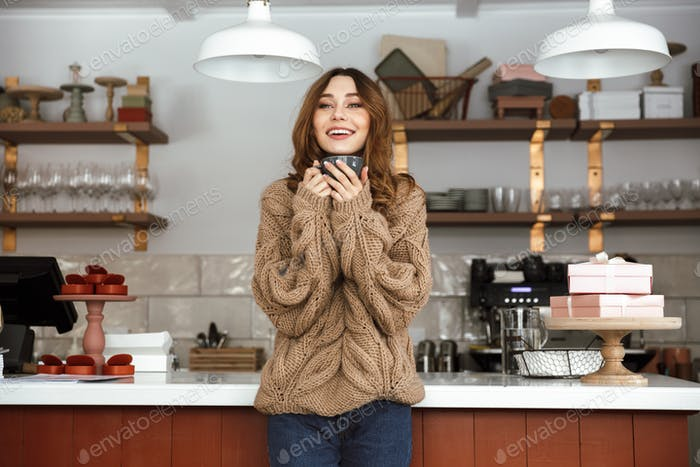 Photo of happy woman in sweater standing near buffet in cafe and
