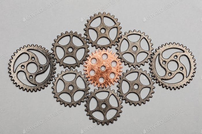 Rose-gold cogwheel and bunch of silver cogwheels