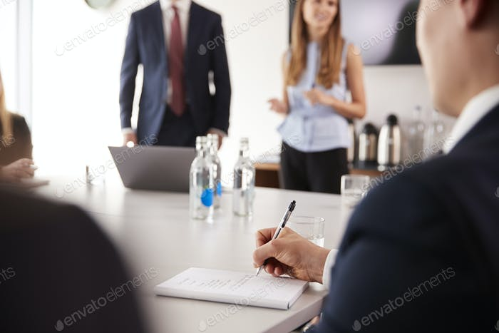 Businessman Making Notes At Group Meeting Around Table On Graduate Recruitment Assessment Day