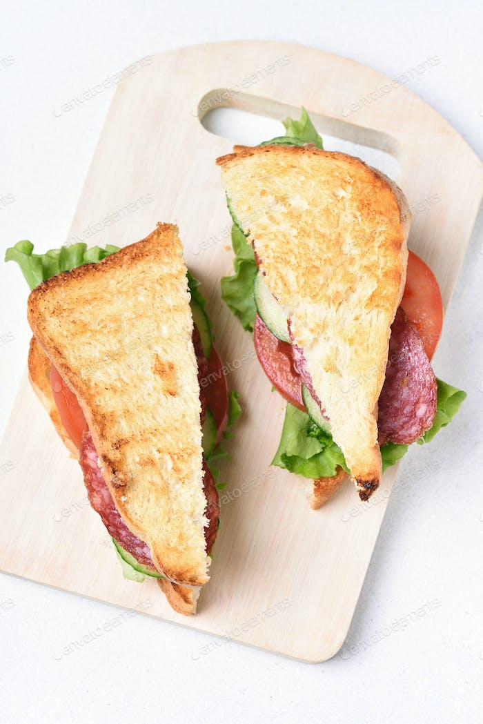 Sandwiches with salami, tomatoes, cucumber and lettuce