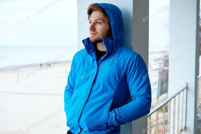 Замерзший человек в голубой толстовке.