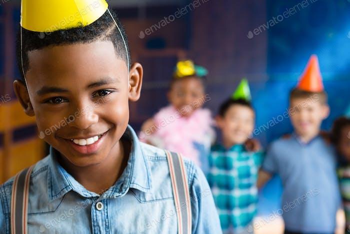 Retrato de niño con tirantes con amigos en el fondo