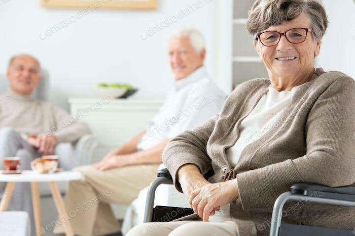 Gelähmte ältere Frau auf Rollstuhl im Pflegeheim, andere pati