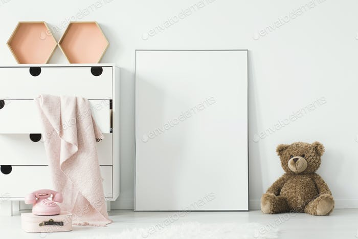 Teddy bear next to white empty poster in baby's room interior wi