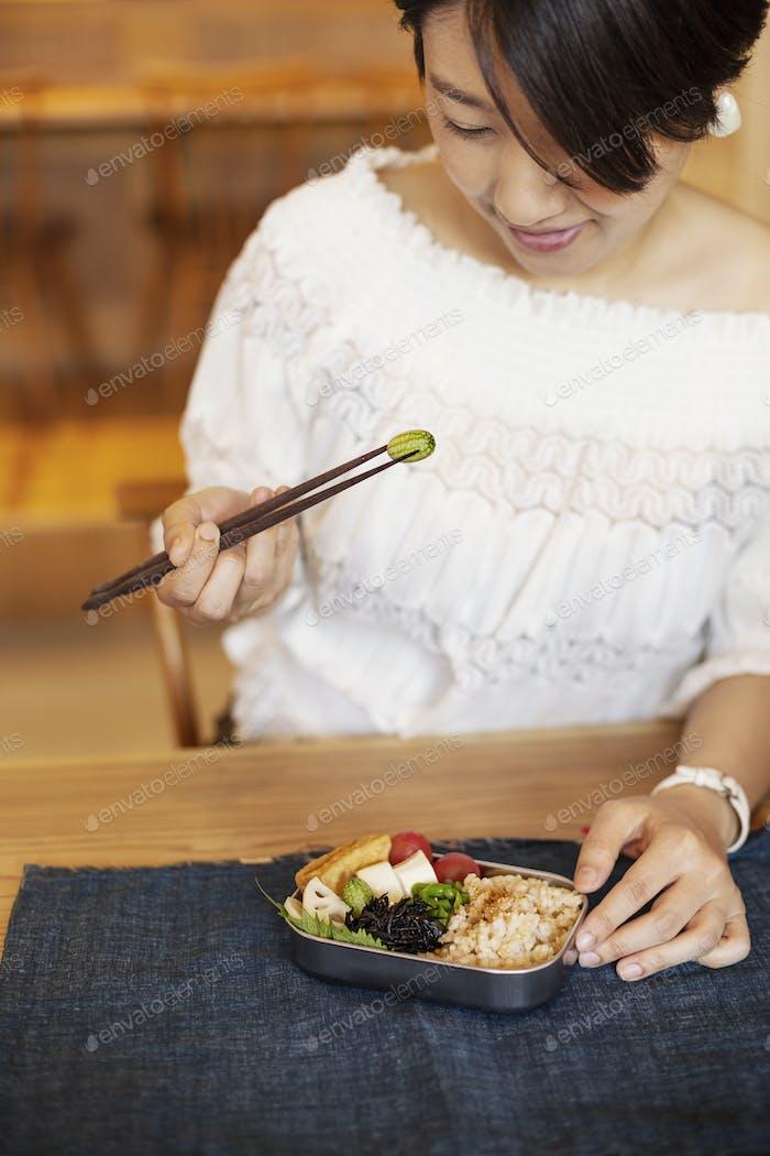 Mujeres japonesas comiendo con palillos en un café vegetariano.