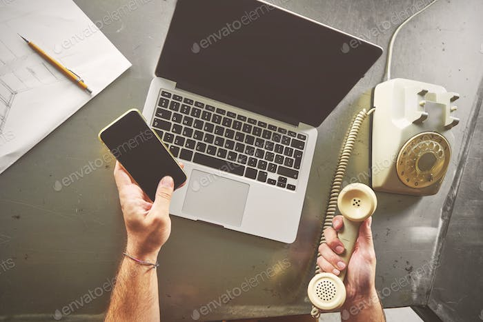 Top view of architect man working at computer and calling his cl