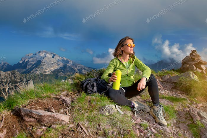 A girl rests after climbing the top of a mountain
