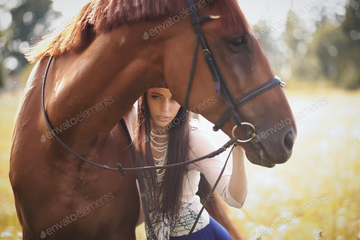 Fashion woman with long brown hair posing with brown horse.