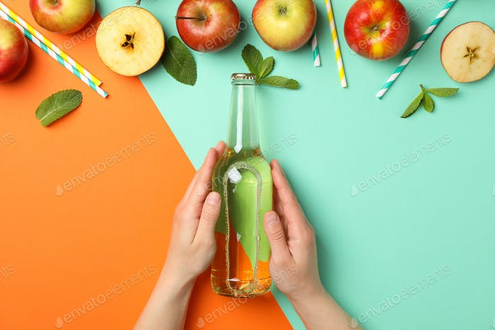 Female hands hold bottle of cider on two tone background. Composition with cider