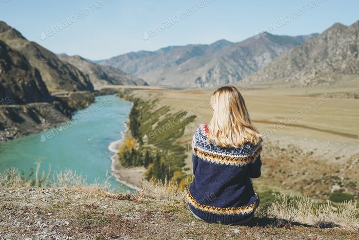 Young blonde woman in nordic sweater sitting on background of the turquoise Katun river