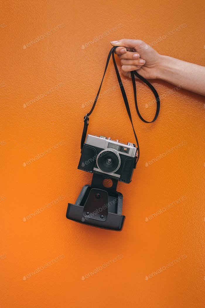 Hand holding a Vintage camera isolated at orange wall