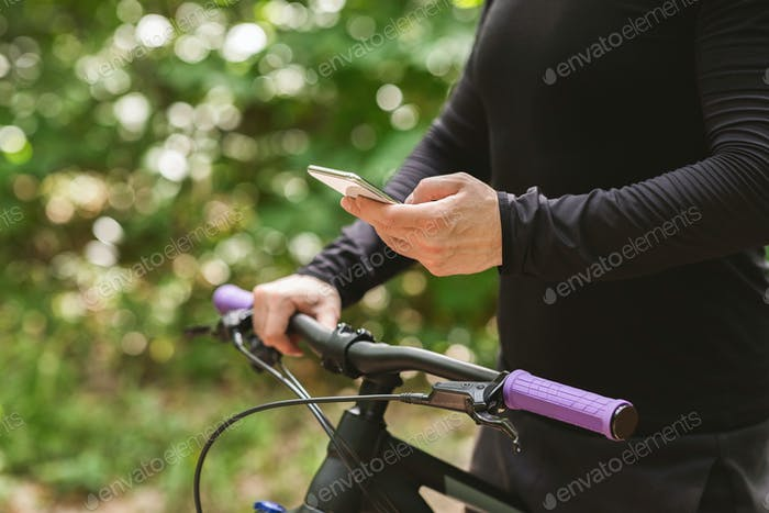 Close up of cyclist holding bike and using phone