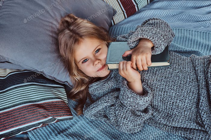 Close-up portrait of a little girl in warm sweater holds storybook while lying on bed.