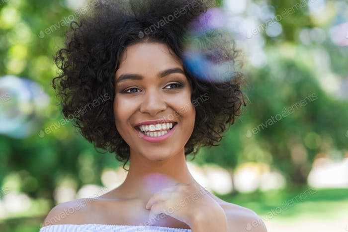 Happy african-american woman surrounded by bubbles in park