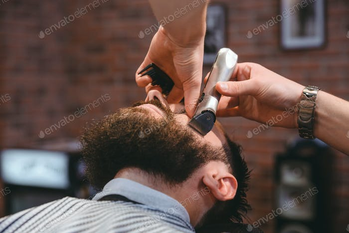 Young bearded man during beard grooming in barber shop