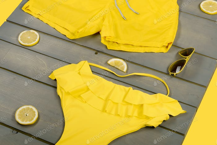 Beach accessories on wooden background. Yellow swimwear one-piece, swim shorts,