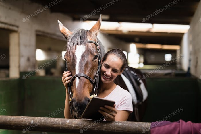 Smiling female jockey using digital tablet while standing by horse