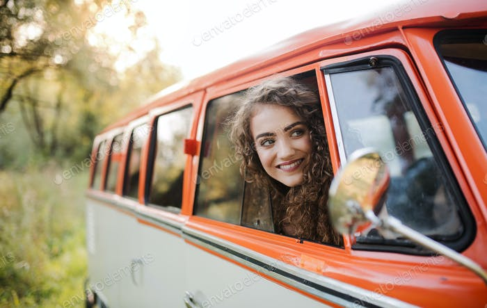 A young girl looking out of a car on a roadtrip through countryside.