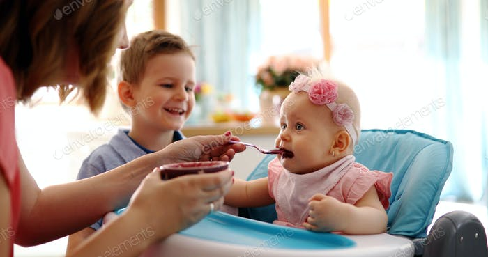 Mother Feeding Her Baby Girl with a Spoon