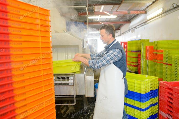 Mann in der Fabrik Waschen Kunststoffkisten