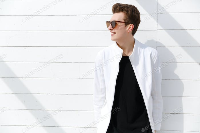Smiling young man in sunglasses over white wall background