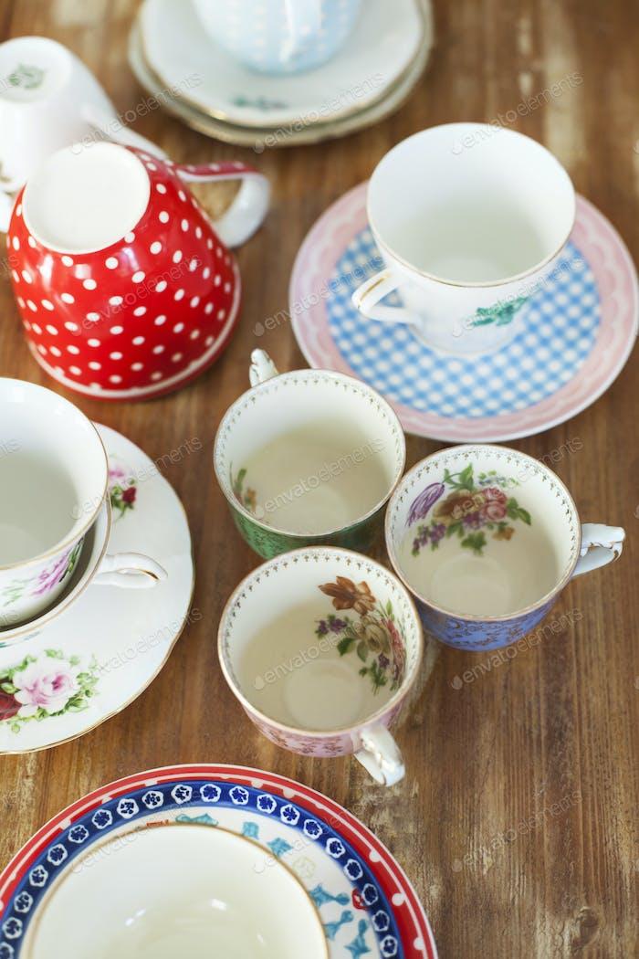 Vielzahl von Teetassen und Untertassen auf Holztisch